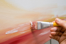 Paintbrush applying paint to a canvas.